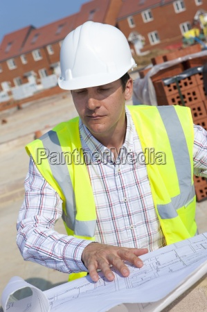 close up of architect reviewing blueprints