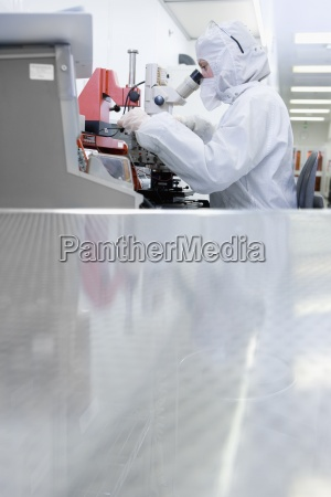 scientist in clean suit examining silicon