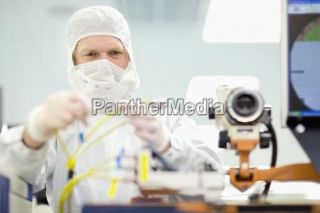 scientist in clean suit adjusting wires