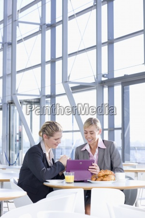 smiling businesswomen using digital tablet and