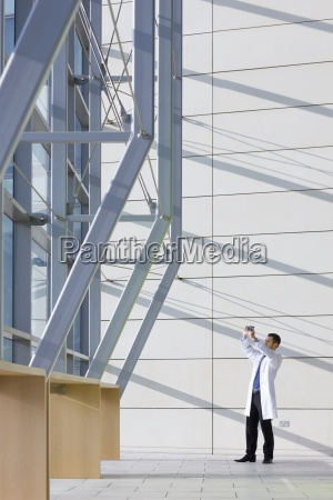 engineer in lab coat examining machine