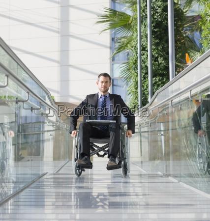 businessman in wheelchair on pedestrian bridge