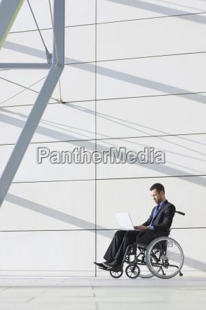 businessman in wheelchair using laptop in