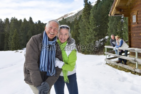 portrait of smiling couples outside cabin