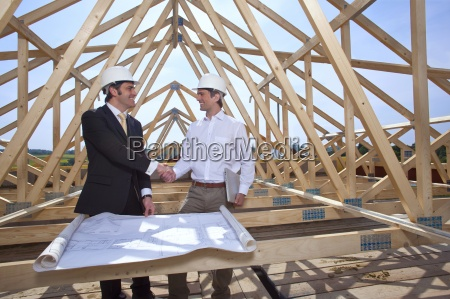 architects with blueprints handshaking at construction
