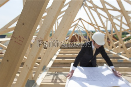 architect reviewing blueprints at construction site