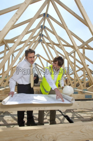 architect and engineer reviewing blueprints at