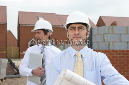 architects holding blueprints at housing construction