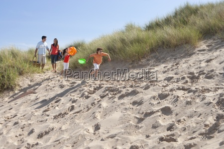 family arriving on sunny beach