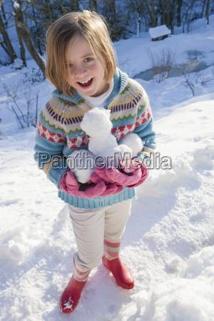 portrait of smiling girl holding snowballs