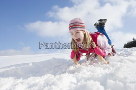 enthusiastic girl sledding down snowy hill