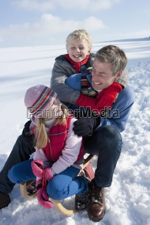 smiling father with daughter and son