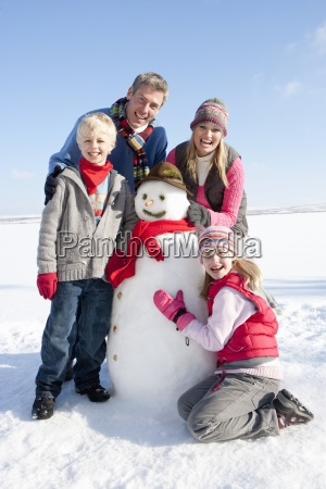 portrait of smiling family with snowman