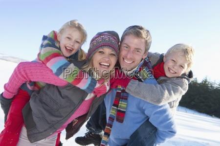 portrait of smiling parents piggybacking daughter