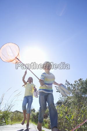 enthusiastic boy and girl holding fishing