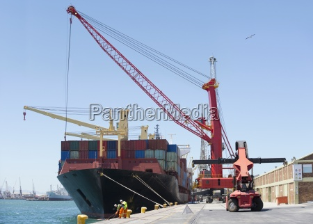 cranes unloading container ship at commercial