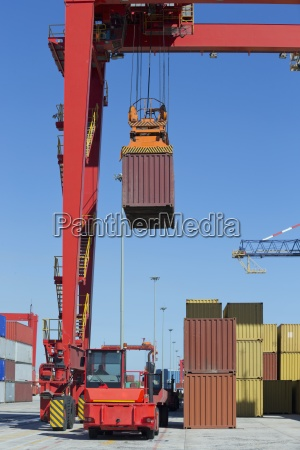 crane lifting cargo container at commercial