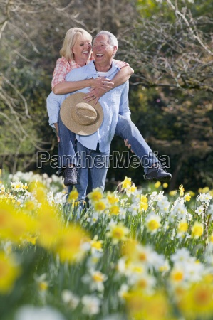 smiling senior couple piggybacking in sunny