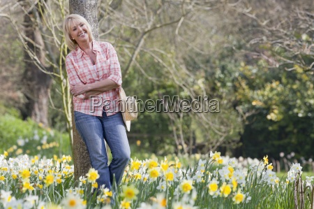smiling woman leaning against tree with
