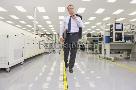businessman walking through hi tech electronics