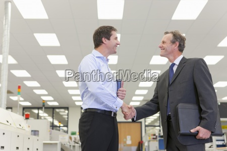 smiling businessmen shaking hands in hi