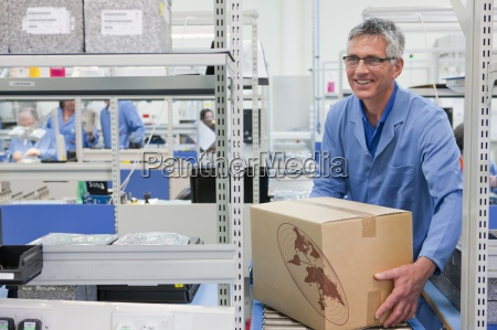 smiling worker lifting cardboard box from