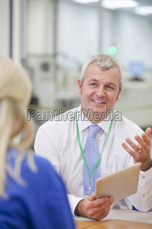 manager with digital tablet talking to