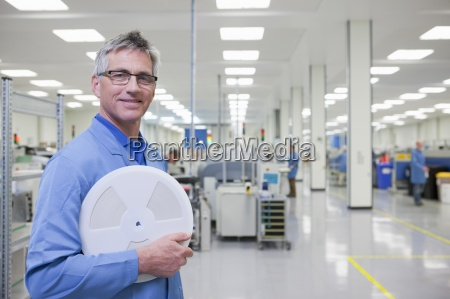 portrait of smiling engineer holding data