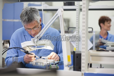 technician working on assembly line in