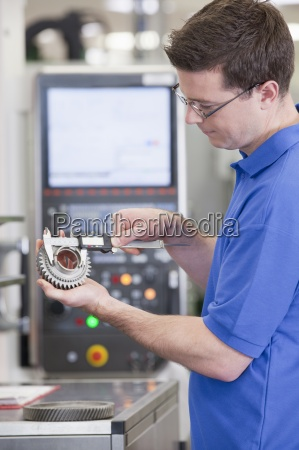 technician measuring gear wheel with vernier