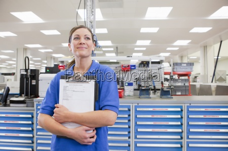 portrait of smiling technician holding clipboard