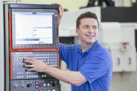 smiling technician controlling lathe cutting machine