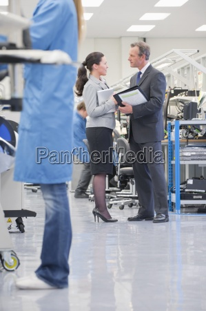 business people meeting in manufacturing plant