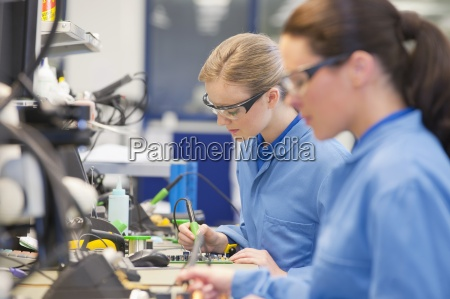 technicians soldering circuit boards on production