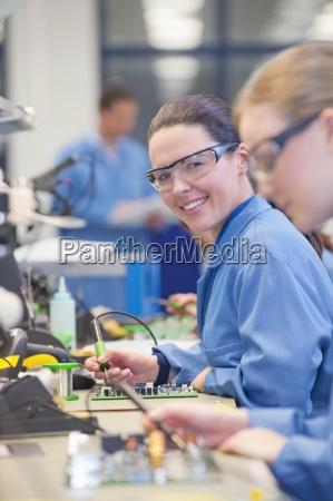 portrait of smiling technician soldering circuit