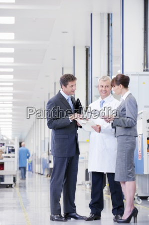 business people and engineer reviewing paperwork