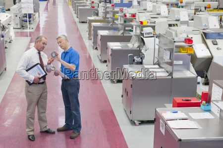 businessman and engineer examining machine part