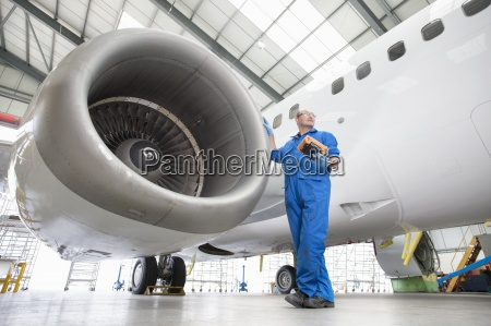 engineer standing next to engine of