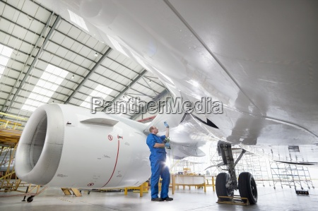 engineer inspecting engine of passenger jet