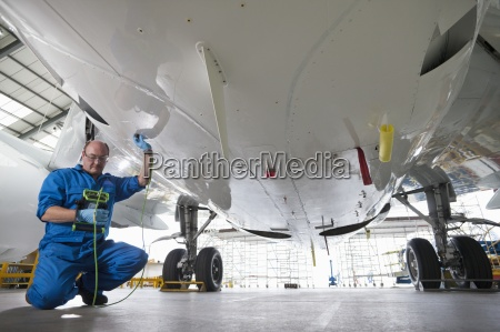 engineer inspecting undercarriage of passenger jet