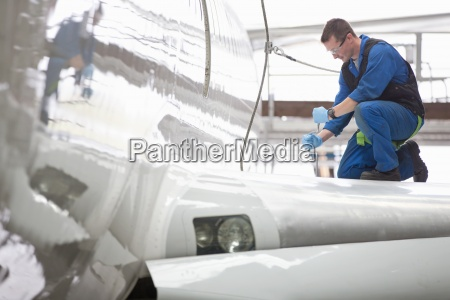 engineer repairing wing on passenger jet