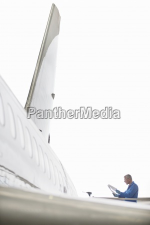 engineer at wing of passenger jet