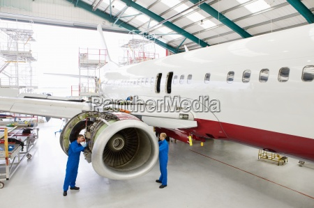 engineers assembling engine on passenger jet