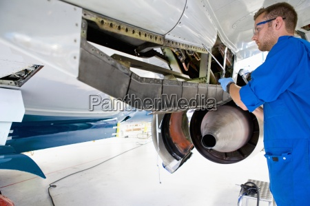engineer working under wing of passenger
