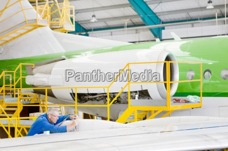 engineer inspecting wing of passenger jet