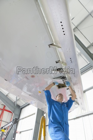 engineer repairing flaps on wing of