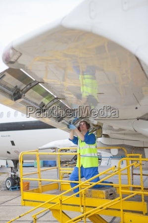 engineer repairing flap on wing of