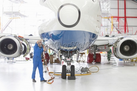 engineer assembling passenger jet in hangar