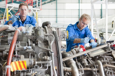engineers repairing engine of passenger jet