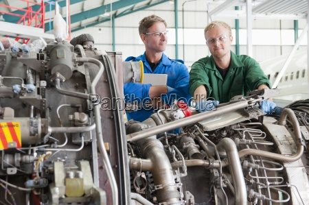 portrait of confident engineers inspecting engine